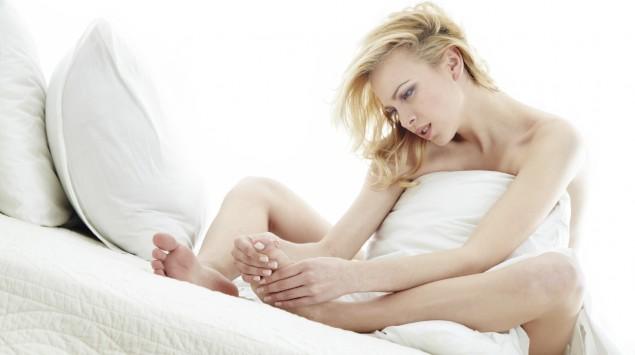 Eine im Bett sitzende Frau fasst sich an den Fuß.