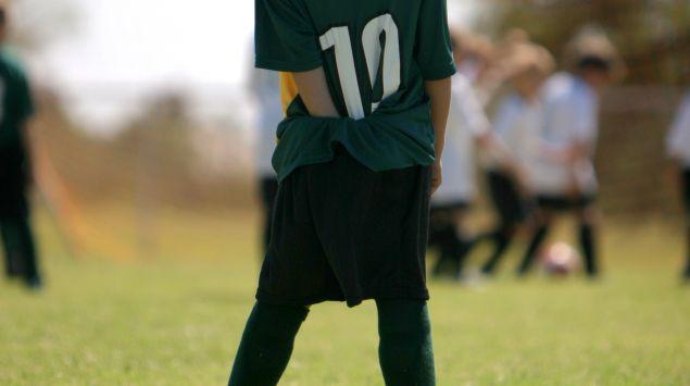 Das Bild zeigt ein Kind, das Fußball spielt.