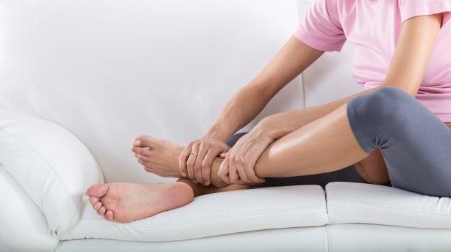 Eine schwangere Frau sitzt auf einem Sofa und reibt sich das linke Fußgelenk.