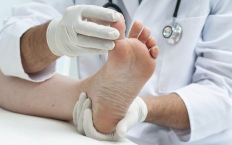 Ein Arzt untersucht einen Fuß.