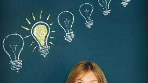 Eine Frau steht vor einer Tafel, auf der mehrere aufgezeichnete Glühbirnen zu sehen sind.