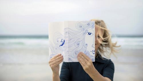 Eine Frau hält eine Zeichnung von ihrem Gesicht vor sich