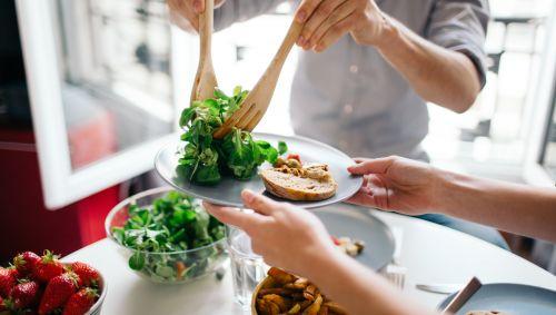 Ein Mann gibt Salat auf den Teller einer Frau.