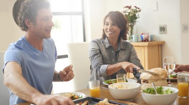 Ein junges Paar sitzt am Tisch und bedient sich an den verschiedenen Essensbeilagen.