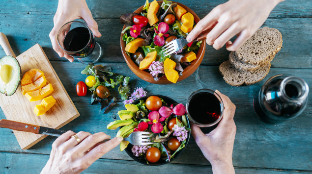 Vitamine: Man sieht zwei Schalen mit gemischtem Salat und Rotweingläser.