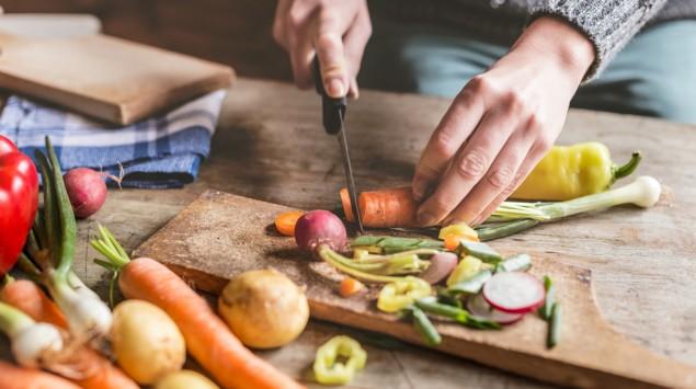 Jemand schneidet auf einem Holzbrett verschiedene Gemüsesorten mit einem Messer klein.