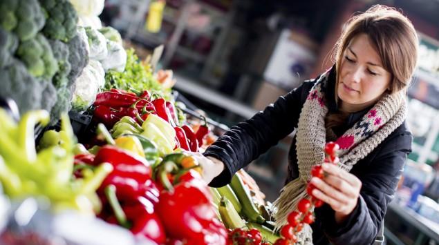 Das Bild zeigt eine Frau beim Gemüsestand.