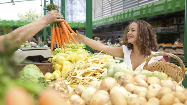 Eine junge Frau lässt sich an einem Gemüsestand ein Bund Möhren reichen.