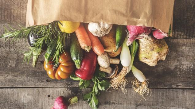Man sieht eine Papiertüte mit einer Gemüseauswahl.