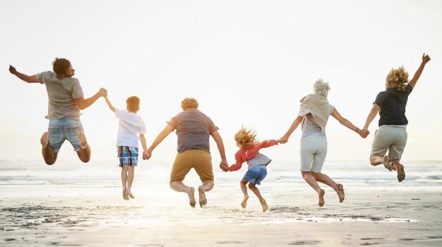 Familie mit drei Generationen springt am Strand