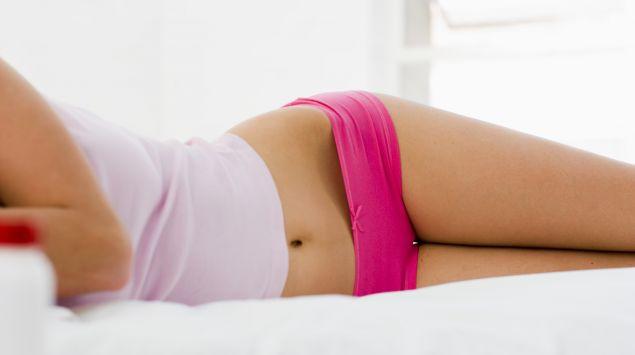 Das Bild zeigt eine Frau, die in Unterwäsche auf dem Bett liegt.