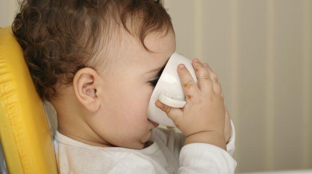 Ein Baby trinkt aus einer Tasse.