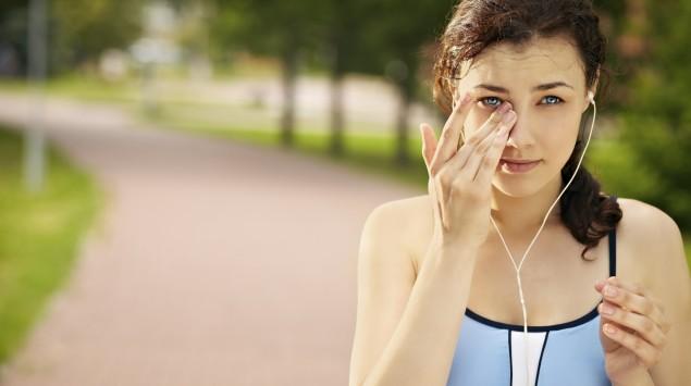 Ein junges Mädchen wischt sich etwas aus dem rechten Auge.
