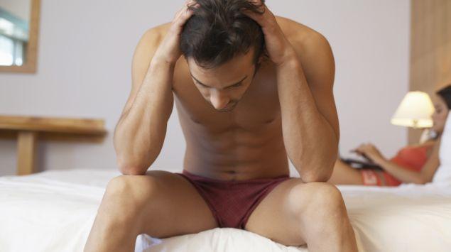 Das Bild zeigt einen halbnackten Mann, der auf einem Bett sitzt.