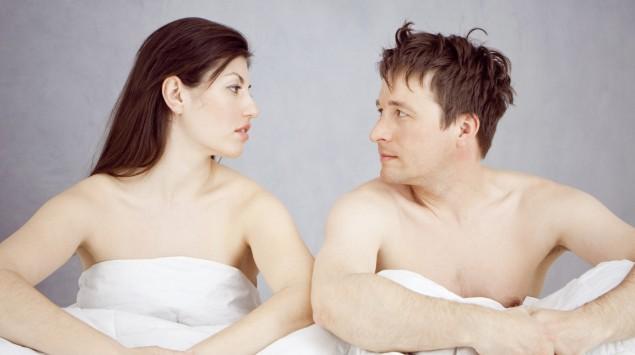 Das Bild zeigt ein Pärchen, das unbekleidet in einem Bett sitzt.