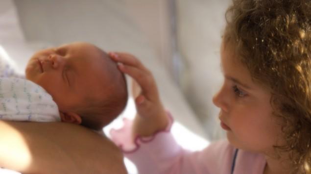 große Schwester streichelt Neugeborenes