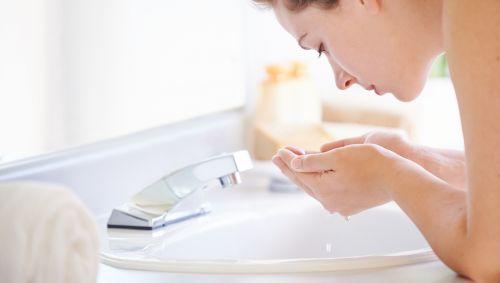 Eine junge Frau wäscht sich ihr Gesicht