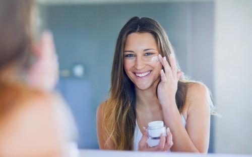 Das Bild zeigt eine junge Frau, die ihr Gesicht eincremt.