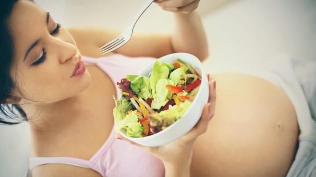 Schwangere Frau isst einen Salat.