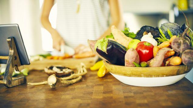 Eine Frau steht in der Küche und schneidet Gemüse.