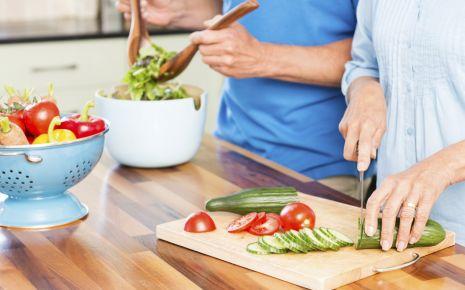 Bluthochdruck senken: Ein Mann und eine Frau bereiten einen Salat zu.