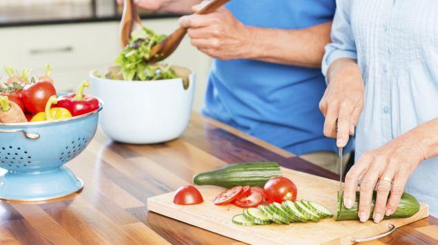 Ein Mann und eine Frau bereiten einen Salat zu.