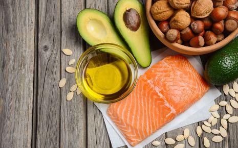 Clean Eating: Man sieht Lachsfilet, eine aufgeschnittene Avocado, Pflanzenöl und Nüsse.