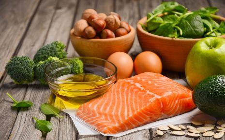 Arthrose: Man sieht ein Lachsfilet, Olivenöl, Brokkoli, Haselnüsse, Eier, Spinatblätter, einen Apfel, eine Avocado und Kürbiskerne.