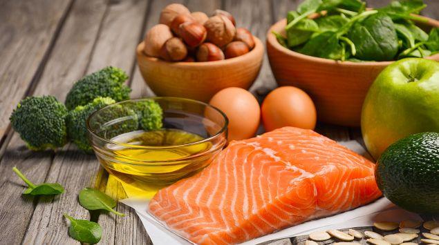 Man sieht ein Lachsfilet, Olivenöl, Brokkoli, Haselnüsse, Eier, Spinatblätter, einen Apfel, eine Avocado und Kürbiskerne.