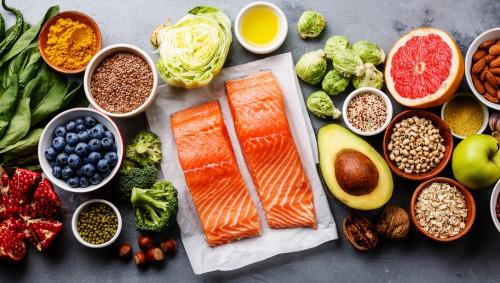 Man sieht eine Auswahl nährstoffreicher Lebensmittel, wie Obst, Gemüse und Lachs.