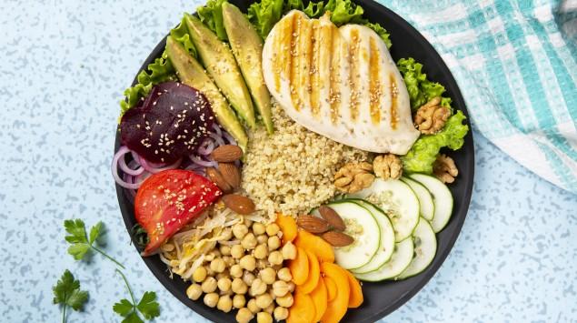 Auf einem Tisch steht eine Schüssel mit gegrilltem Hühnchen, Kichererbsen, Quinoa, Avocado, roter Bete, Tomaten, Karotten, Salatgurke, Salatblättern und Nüssen