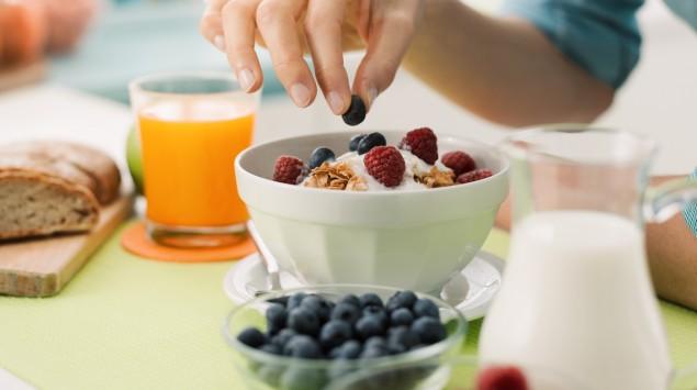 Eine Frau bereitet ein Frühstück mit Müsli und Obst vor.