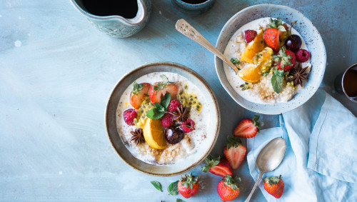 Zwei Schalen mit Müsli und Früchten auf einem blauen Tisch.