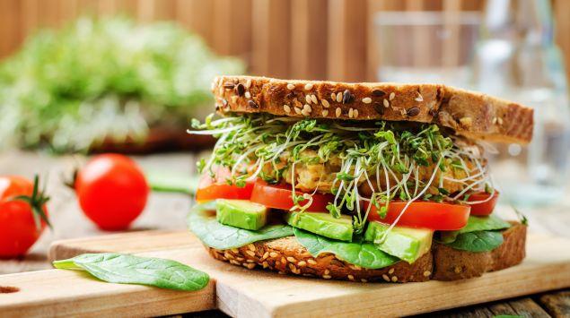 Man sieht ein Vollkorn-Sandwich mit Spinat, Avocado, Tomate, Kichererbsen und Kresse.
