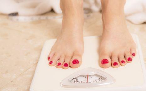 Bluthochdruck senken: Man sieht die Füße einer Frau auf einer Waage.