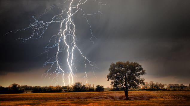 Ein Gewitter über einem Feld mit einem einzelnen Baum.