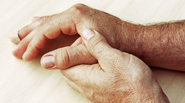 Jemand hält seine schmerzende Hand.
