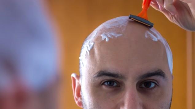 Ein Mann rasiert sich eine Glatze.