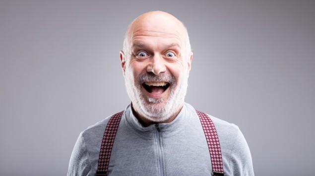 Mann mit Glatze lacht übertrieben in die Kamera