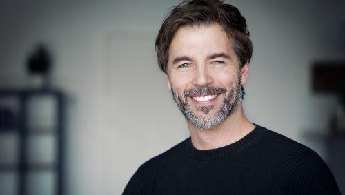 Das Bild zeigt das Porträt eines glücklichen Mannes.