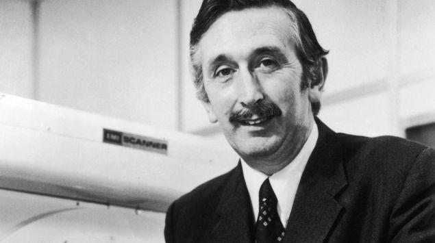 Sir Godfrey Newbold Hounsfield steht vor einem Ct-Gerät.