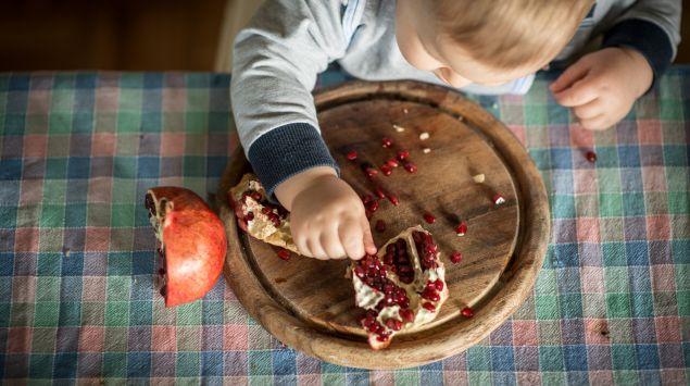 Ein Baby isst Granatapfel.