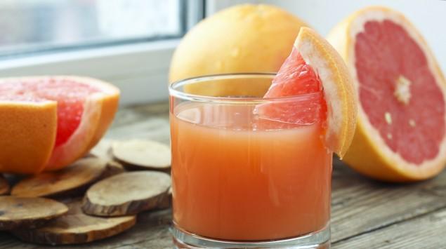 Man sieht ein Glas mit Saft und mehrere Grapefruits.