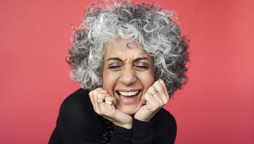 Eine lachende Frau mit lockigen grauen Haaren vor rotem Hintergrund