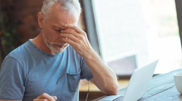 Ein grauhaariger Mann sitzt an einem Tisch vor einem Laptop und greift sich mit der linken Hand an die Nasenwurzel.