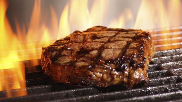 Ein Stück Fleisch inmitten von Flammen auf einem Grillrost.