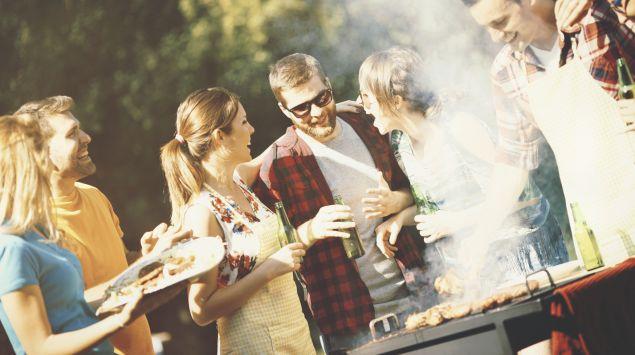 Eine Gruppe fröhlicher junger Männer und Frauen feiert eine Grillparty.