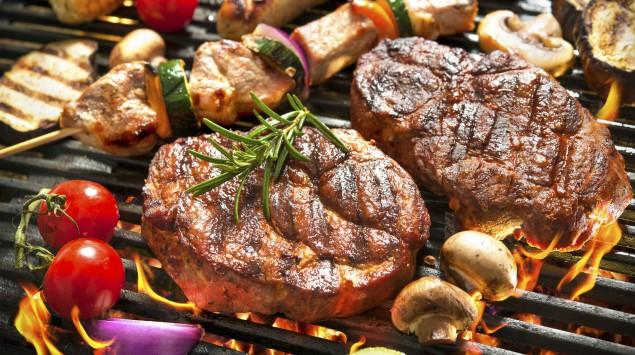 Ein vollbeladener Grill mit Fleisch und Gemüse.