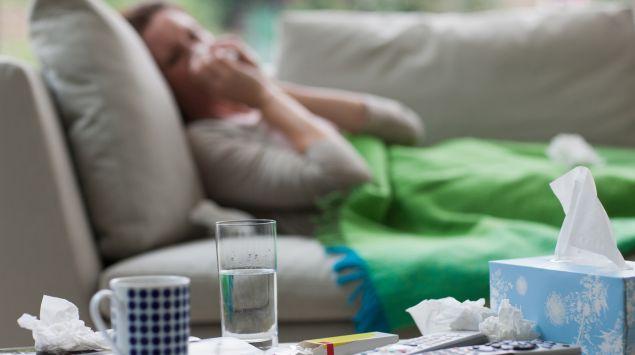 Eine Frau liegt auf der Couch und putzt sich die Nase, im Vordergrund sieht man eine Tasse, ein Glas Wasser, Taschentücher und Medikamente.