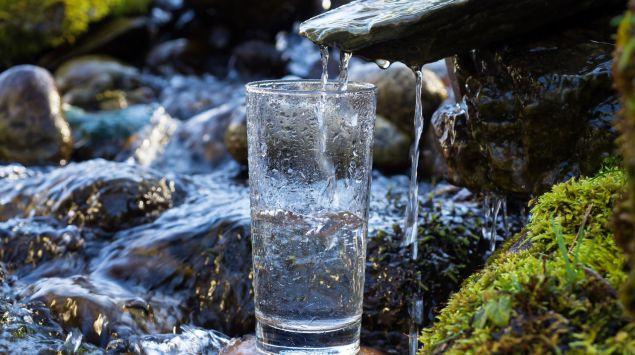 Das Bild zeigt ein Glas unter einer Quelle mit Wasser.